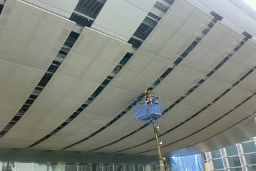 Cable metal mesh is used in the airport roof, and a person is maintaining the roof.