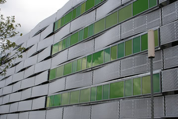 Several rows of expanded metal mesh alternates with green glass and are installed on the building as the cladding.