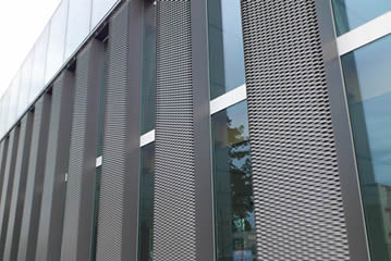 Expanded metal mesh alternates with glass decorating the building.