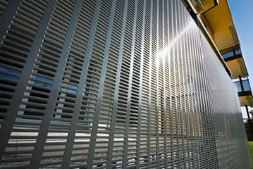 Perforated metal mesh with rectangle holes is installed on the building as the cladding.