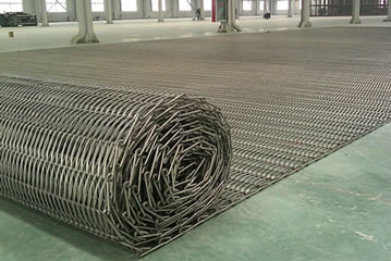 A roll of conveyor belt mesh on the floor.